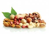 stock photo of mixed nut  - assortment of tasty nuts with leaves - JPG