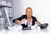 a woman in the office with paper balls. anger, stress and frustration in the workplace