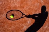 shadow of a tennis player in action on a tennis court (conceptual image with a tennis ball lying on