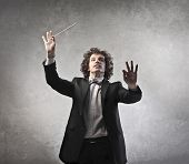 stock photo of conduction  - Man conducting an orchestra - JPG