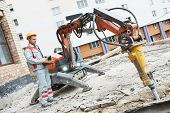 pic of millwright  - builder worker in safety protective equipment operating construction demolition machine robot - JPG