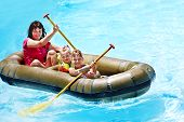 Family with children  ride  rubber boat at  swimming pool .