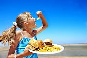 Child eating fast food at beach outdoor.