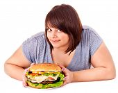 Overweight woman holding big hamburger.