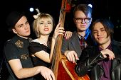 Three young men and beautiful woman with contrabass from music band pose.
