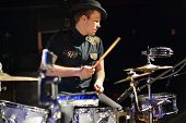 foto of bonaparte  - Handsome man in hat and black shirt plays drum set in night club - JPG