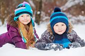 Smiling little girl and boy lie side by side on snowdrift in winter park
