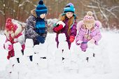 stock photo of brick block  - Children work at building wall from snow blocks in winter park - JPG