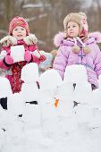 Two little girls build wall from snow blocks in winter park