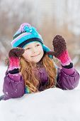 Smiling rosy girl in jacket, knitted hat and mittens lies on snowdrift