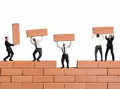 stock photo of erection  - Teamwork builds a new business with bricks - JPG