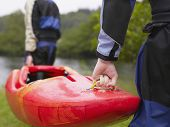stock photo of canoe boat man  - Rear view of two men carrying red kayak to river - JPG