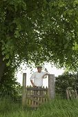 Portrait of a smiling man standing across field gate under the tree