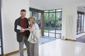 Happy couple reading brochure in new property