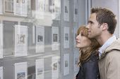 picture of side view people  - Side view of a young couple looking at window display at real estate office - JPG