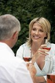 Happy woman looking at man while having red wine at lawn