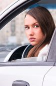 sensual young woman is looking at camera from a car