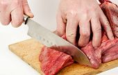 Hands of butcher cutting slices of fresh meat