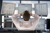 pic of multitasking  - Rear view of stock trader with hands on head looking at multiple computer screens - JPG