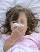 sick child in bed sneezing with tissue