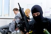foto of shoplifting  - Photo of terrorist in balaclava holding gun on background of bound office workers - JPG