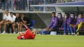 MALAGA, SPAIN. 19/09/2010.  A Sevilla player rolls on the floor injured and watched by the Malaga te