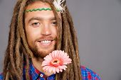 Portrait of a hippie young man with a flower.