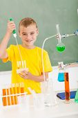 smiling primary schoolboy pouring liquid in tubes in science class