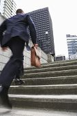 picture of ascending  - Full length rear view of a businessman with briefcase ascending steps - JPG