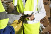 stock photo of labourer  - Midsection of two workers holding clipboards in industry - JPG