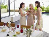 Tres jóvenes amigas tostado flautas de champán en la cena