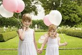 Portrait of cute little bridesmaids with balloons holding hands in garden