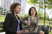 Two smiling businesswomen sitting on park bench with waterbottle and coffee cup