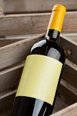 stock photo of wooden crate  - White wine bottle with empty label in wooden crate - JPG