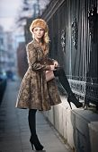 Attractive elegant blonde young woman wearing an outfit with Russian influence in urban fashion shot