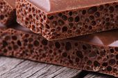 Aerated Milk Chocolate On Old Wooden Table Closeup