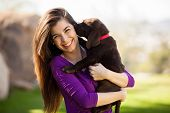 stock photo of labradors  - Happy young woman hugging and having fun with her Labrador puppy outdoors - JPG