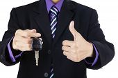 Businessman Offering A Car Key With Thumbs-up