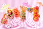 Different colorful fruit candy in glasses on pink background