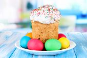 Sweet Easter cakes with colorful eggs on table in room