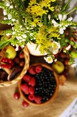 Still life with flowers and berries on wooden table