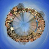 360 degree view of Amsterdam canal houses around the circumference of a watery planet with reflectio