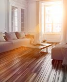 Bright sunlight streaming into a living room interior with a parquet floor and couch through a large