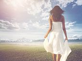 Slender long-haired woman wearing white summer dress while walking on a green meadow towards a brigh