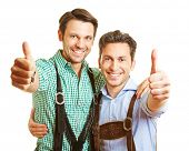 Two happy bavarian men in leather pants holding their thumbs up