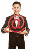 Smiling businessman holding big red at sign as internet symbol