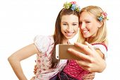 Two happy women in dirndl dress taking selfie with smartphone