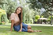 Full length of smiling young woman looking away while relaxing in park