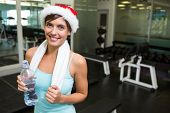 Fit brunette in santa hat smiling at camera at the gym