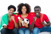 Cheering football fans in red sitting on couch with portugal flag on white background
